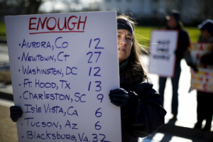 a woman holds a sign listing victims of gun violence | Presbyterian Peace Fellowship