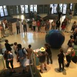 A circle of people gathered in a lobby next to a giant earth ball