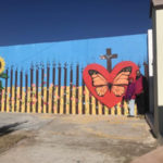 Two people stand in front of the US-Mexico border fence in Agua Prieta, painted as a mural with a butterfly in the center of a heart.