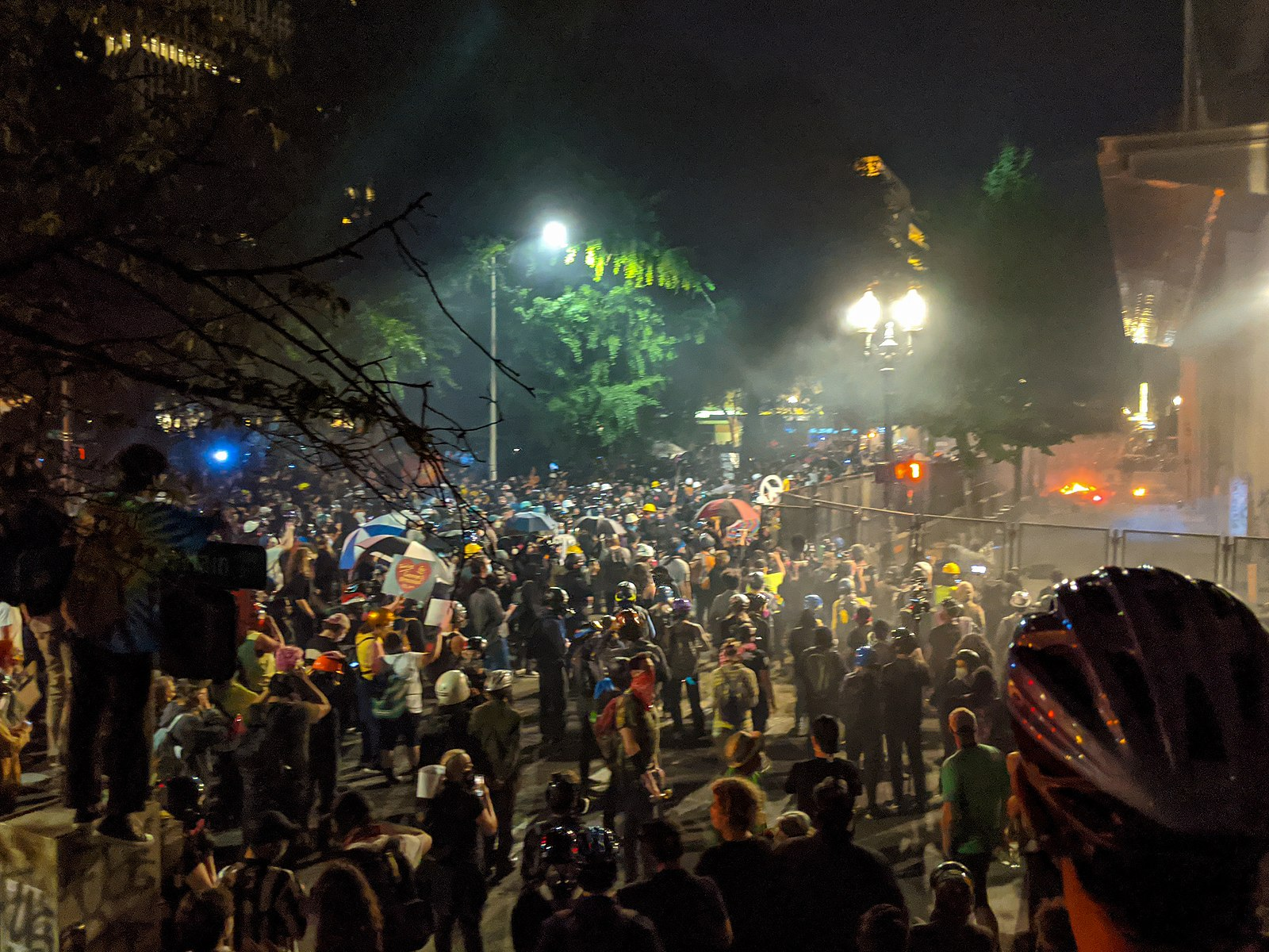 Large crowd gathered at night in protests in Portland Oregon in front of Justice Center where teargas was used